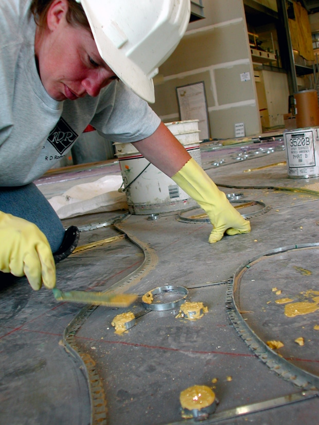 Beth from R.D. Roman Terrazzo works on the yellow terrazzo fills